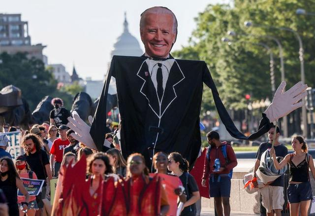 FILE PHOTO: Environmental activists march towards the White House to demand U.S. President Joe Biden stop fossil fuel projects and put climate justice at the heart of his infrastructure plans, in Washington, U.S., June 30, 2021. REUTERS/Evelyn Hockstein