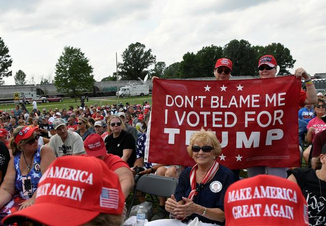 FILE PHOTO: Supporters of former U.S. President Donald Trump hold a banner during his first post-presidency campaign rally at the Lorain County Fairgrounds in Wellington, Ohio, U.S., June 26, 2021. REUTERS/Gaelen Morse